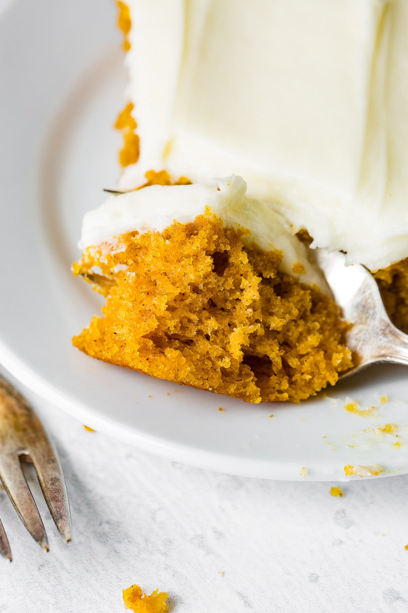 A photo of someone removing a bite of pumpkin sheet cake with a fork.