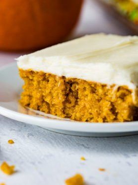 A photo of a piece of pumpkin sheet cake with cream cheese frosting sitting on a white plate.