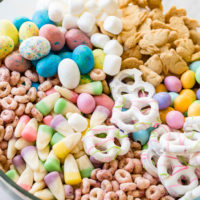 Easter snack mix in a clear glass bowl with berry Cheerios, Easter candy corns, yogurt covered pretzels, Robin eggs, Easter M&Ms. mini marshmallows and bunny cookies.