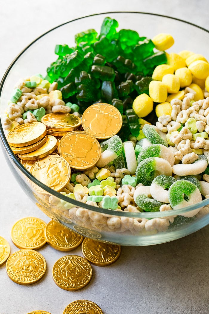 A photo of a large glass bowl full of St. Patrick's Day treats like chocolate gold coins, Lucky Charms, lemon drops, green apple gummy rings, and green gummy bears.