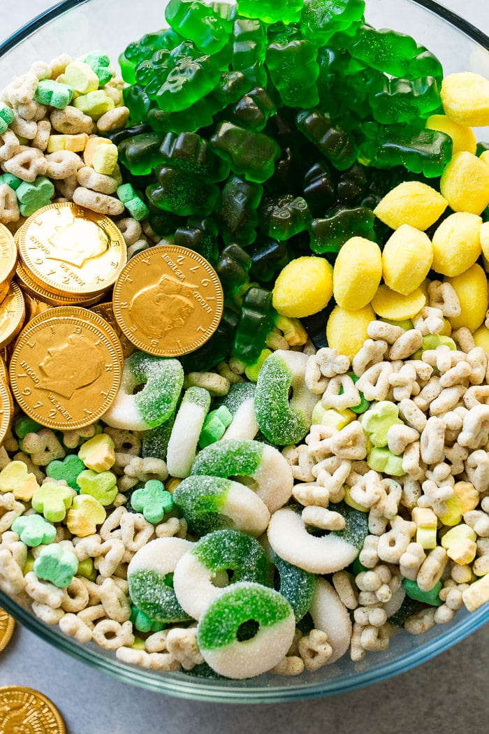 A closeup photo of a large glass bowl full of St. Patrick's Day treats like chocolate gold coins, Lucky Charms, lemon drops, green apple gummy rings, and green gummy bears.