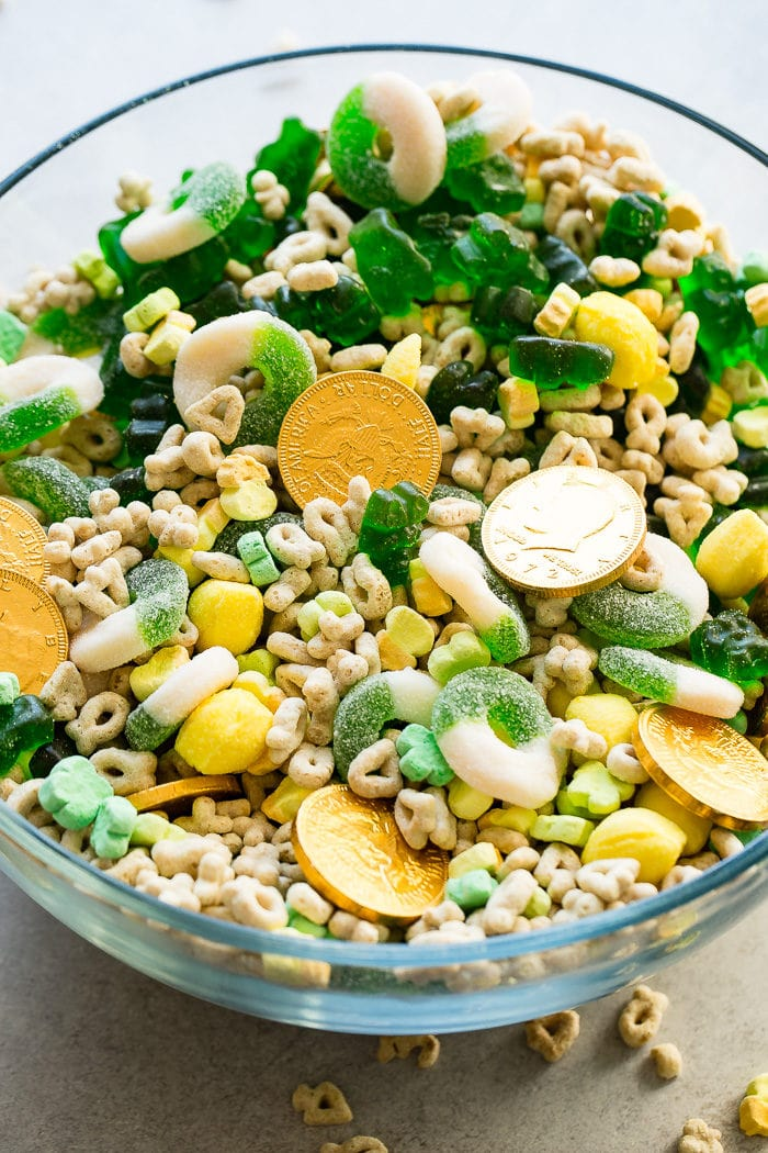 A photo of a large glass bowl full of St. Patrick's Day treats all mixed together like chocolate gold coins, Lucky Charms, lemon drops, green apple gummy rings, and green gummy bears.