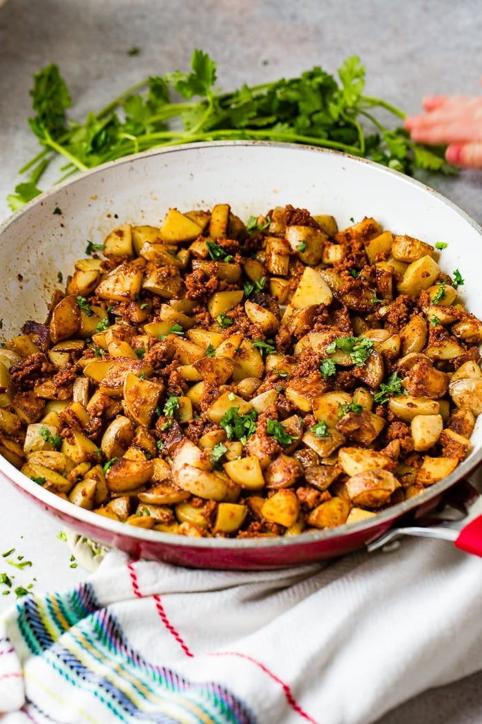 a red and white skillet with quick and easy 3 ingredient chorizo potatoes with cilantro on top