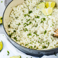 A photo of a pot full of cilantro lime cauliflower rice with fresh lime wedges sitting on top and a wooden spoon in it.