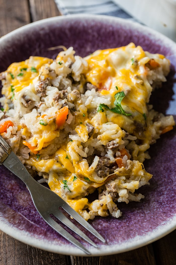 a purple plate with a fork with a wood handle next to a ground beef and rice casserole full of bits of bright orange carrots and melted colby jack cheese all over the top.