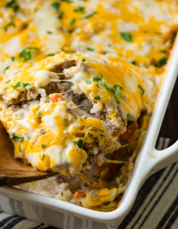 a wooden spoon scooping a ground beef, rice and carrots casserole with melted cheese on the top