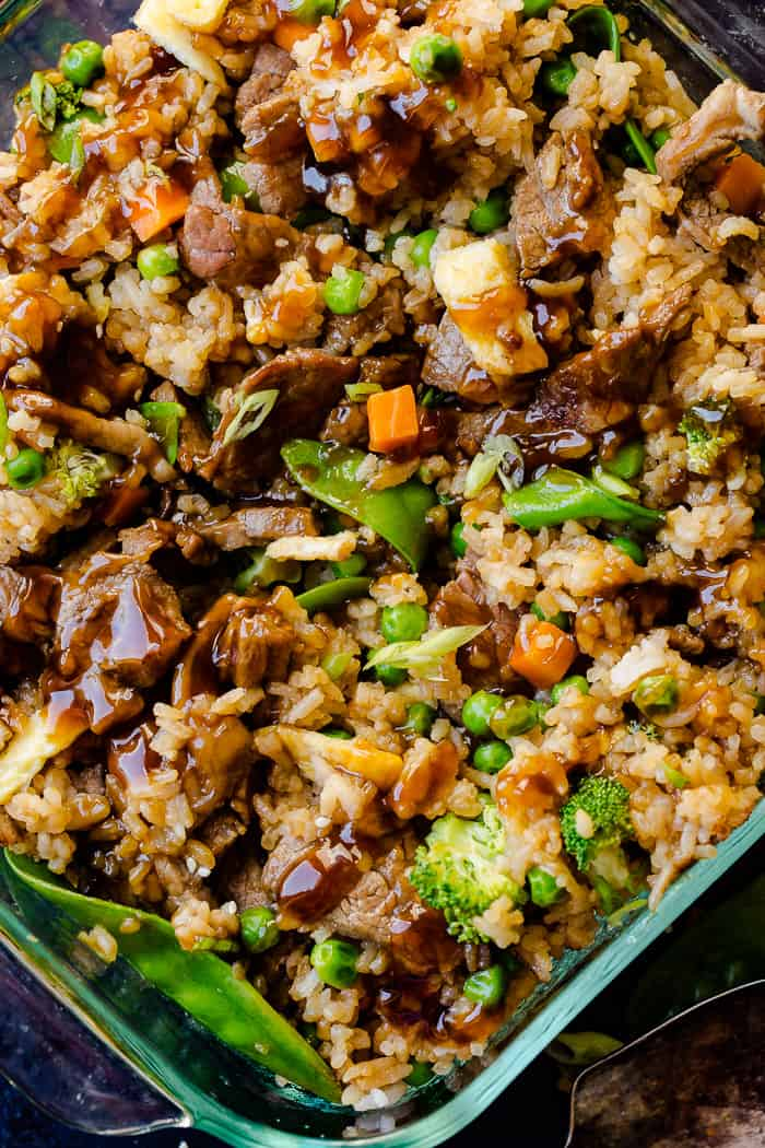a glass casserole dish with fried rice, carrots, peas, broccoli, snow peas, and teriyaki beef