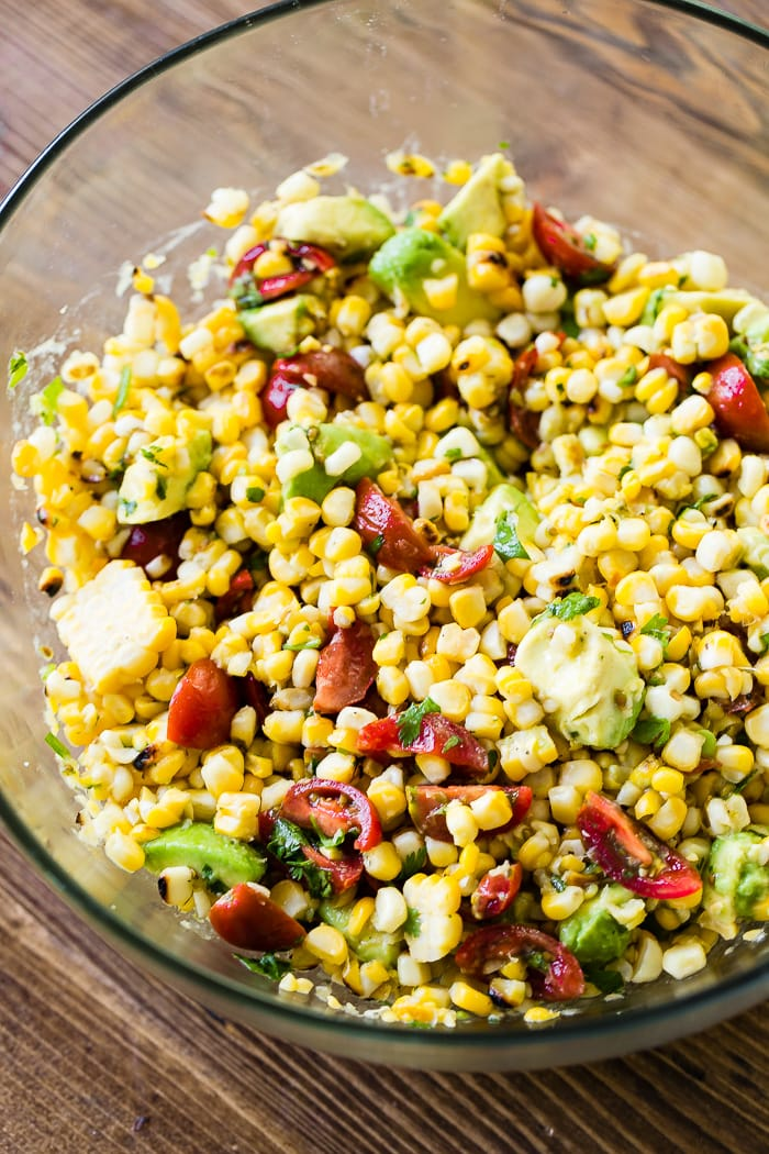 a close up of a fresh grilled corn salad with tomatoes and avocados!