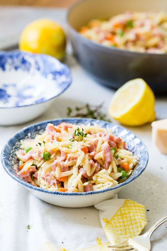 A vintage blue patterned bowl on a white and yellow napkin filled with quick and easy lemon orzo, ham, peas, carrots and parmesan cheese with lemons and thyme in the background