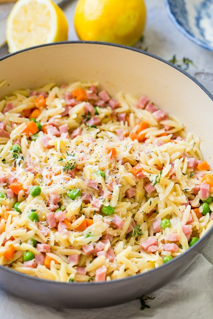 A grey le creuset pan with ham lemon orzo with parmesan and peas and carrots and little bits of thyme.