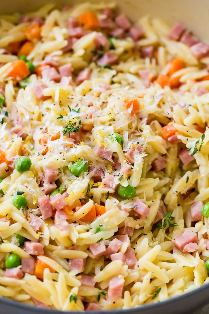 A close up shot with ham lemon orzo with parmesan and peas and carrots and little bits of thyme.