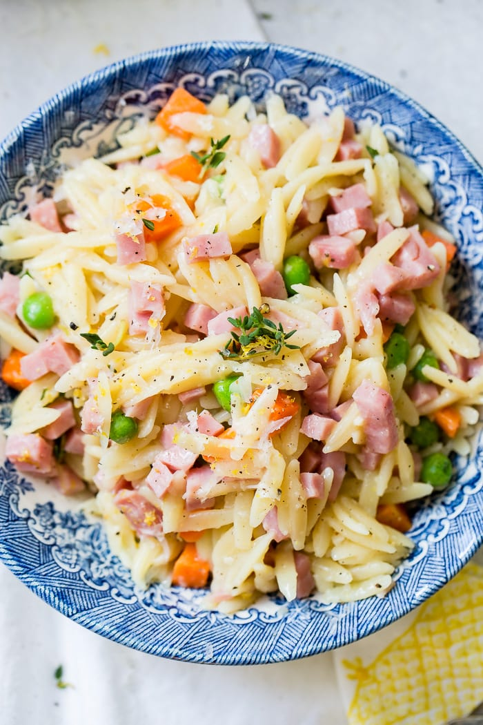 A vintage blue patterned bowl on a white and yellow napkin filled with quick and easy lemon orzo, ham, peas, carrots and parmesan cheese!