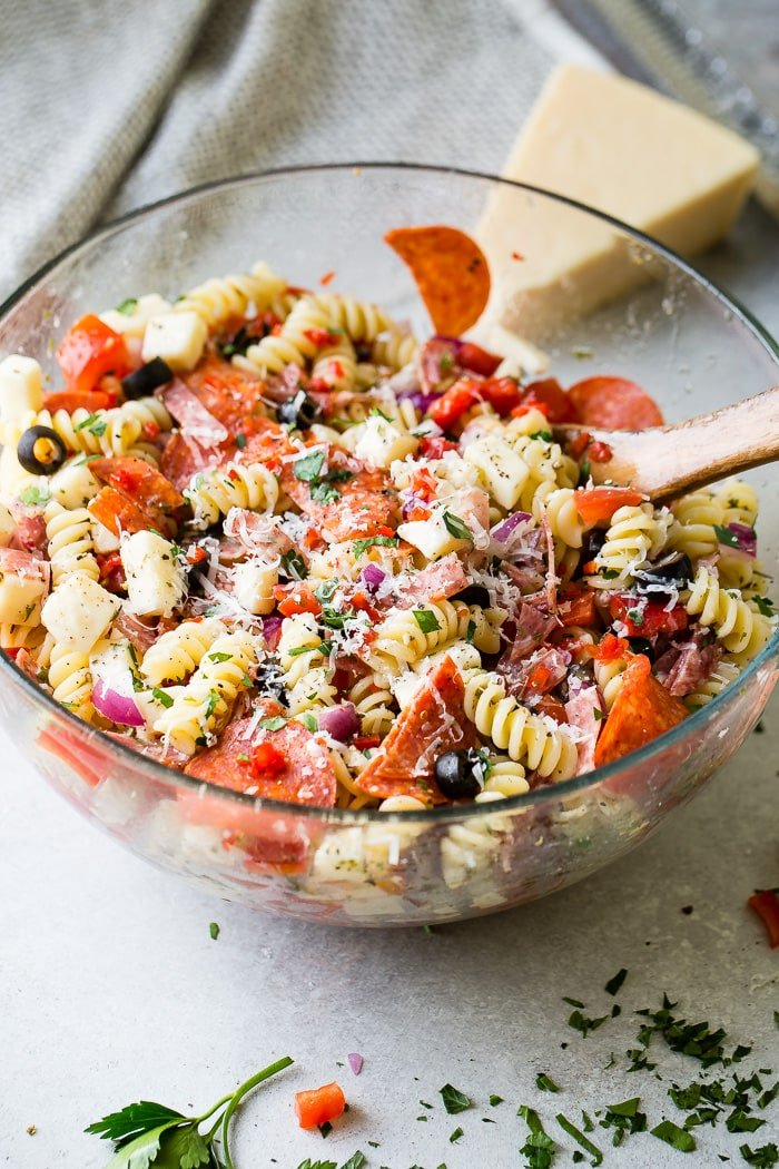 A glass bowl of quick and easy italian pasta salad recipe with homemade italian dressing. Rotini pasta with pepperoni, salsami, black olives, parmesan cheese, mozzarella cheese, peppers, dressing and red onions!