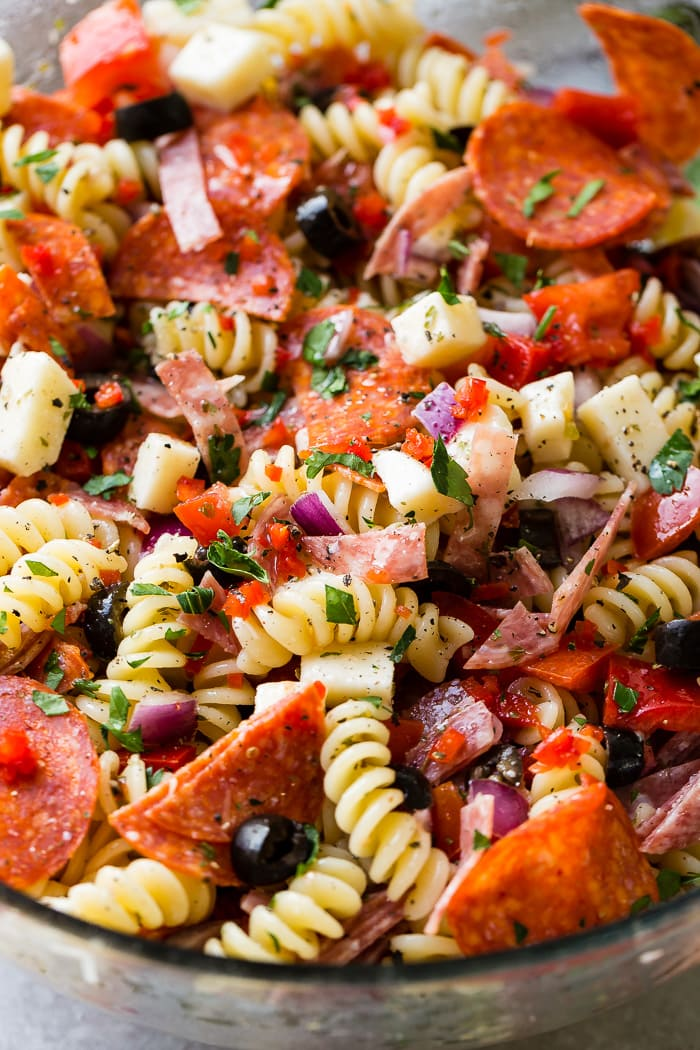 A close up of rotini pasta salad with pepperoni, mozzarella and parmesan cheese, black olives, red peppers, salami and more!