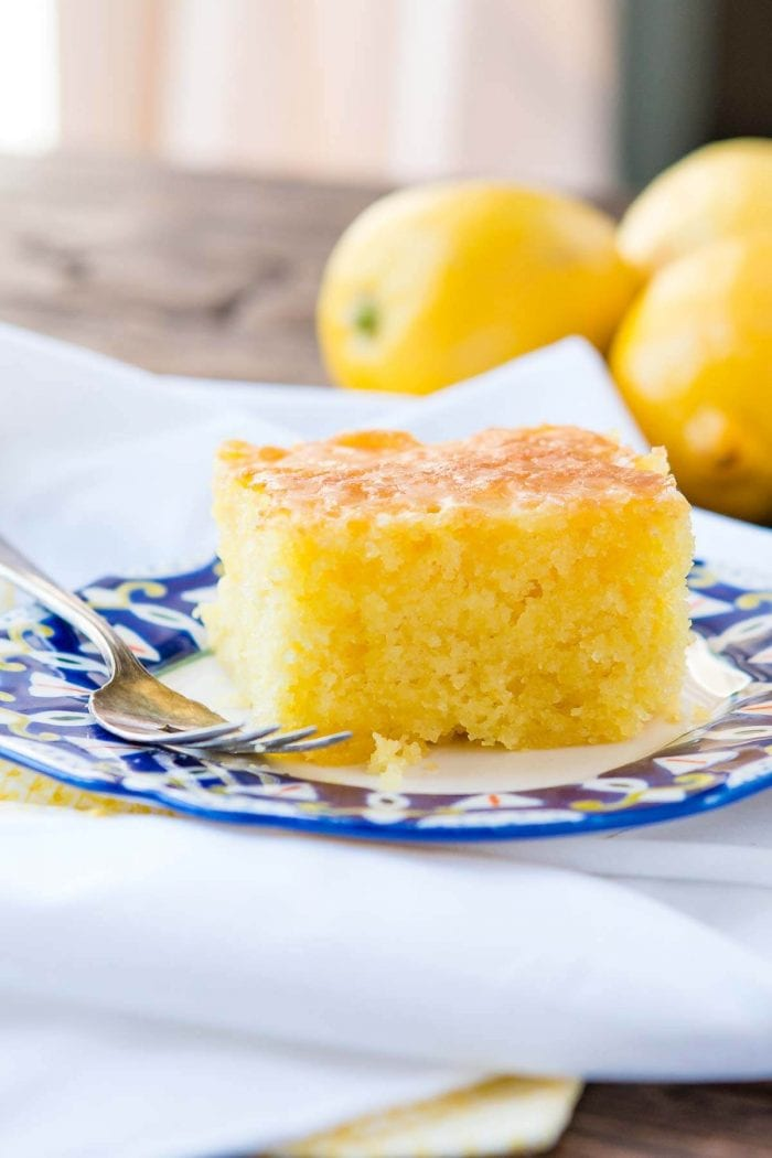 Slice of Lemon Jello Cake on top of a decorative plate with a silver fork.