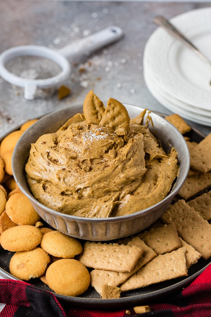 a silver bowl full of fluffy gingerbread cookie dip or molasses cookie dip with graham crackers and nilla wafers