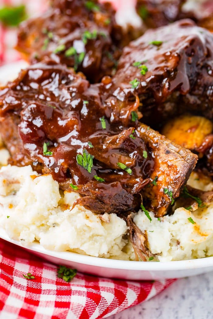 A photo of sticky bbq beef short ribs piled on top of mashed potatoes on a white plate on top of a red and white checkered cloth napkin.