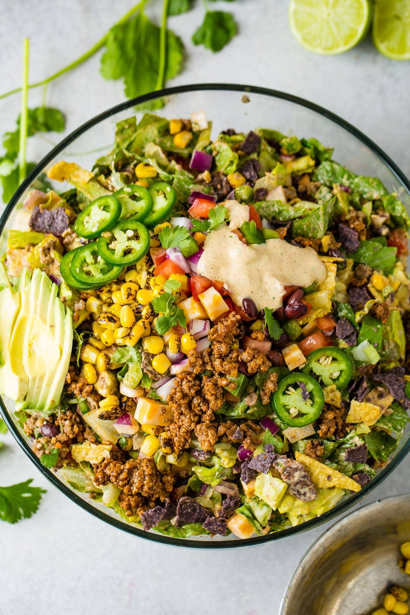 A top view of a large glass bowl of tex-mex taco salad. It is loaded with lettuce, corn, avocado, tomatillas and taco meat. There is a little dressing poured in the top part of the salad.