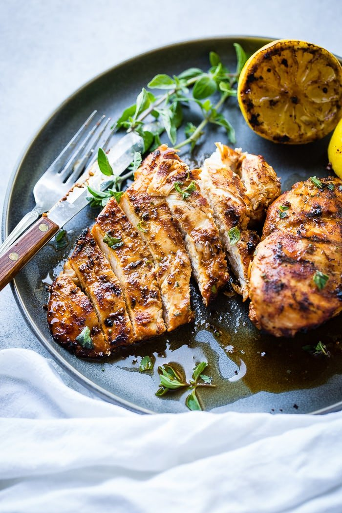 A grey plate with a sliced quick grilled chicken with oregano with oregano and grilled lemons behind it and sitting on a white napkin