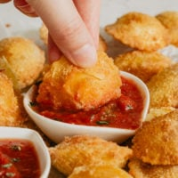 a plate full of easy fried ravioli with one being dipped in marinara sauce
