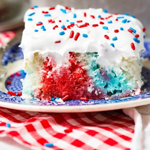 A piece of red, white and blue poke cake on a blue and white dessert plate. The cake is frosted with white frosting and sprinkled with red, white and blue sprinkles. You can see the red, white and blue portions of the cake where holes have been poked and jello poured in. the plate is sitting on a red and white checkered napkin.