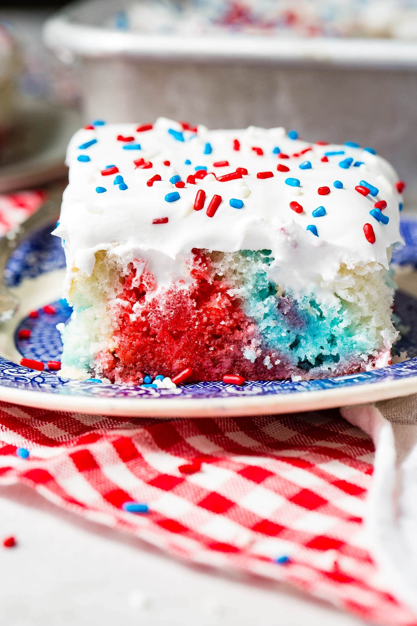 A piece of red, white and blue poke cake on a blue and white dessert plate. The cake is frosted with white frosting and sprinkled with red, white and blue sprinkles. You can see the red, white and blue portions of the cake where holes have been poked and jello poured in.