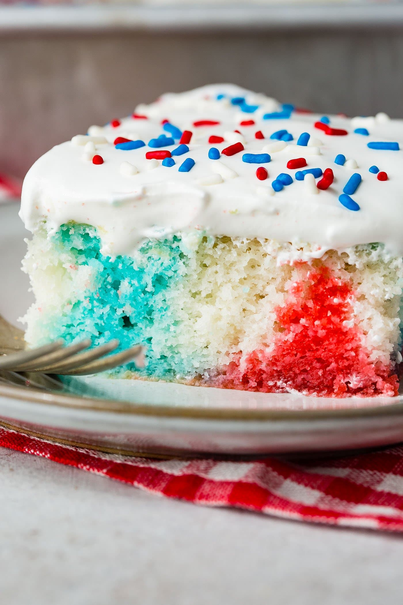 A piece of poke cake with a fork resting next to the cake. The cake is red, white and blue and is topped with white frosting and red, white and blue sprinkles. It is sitting on a red and white checked napkin.