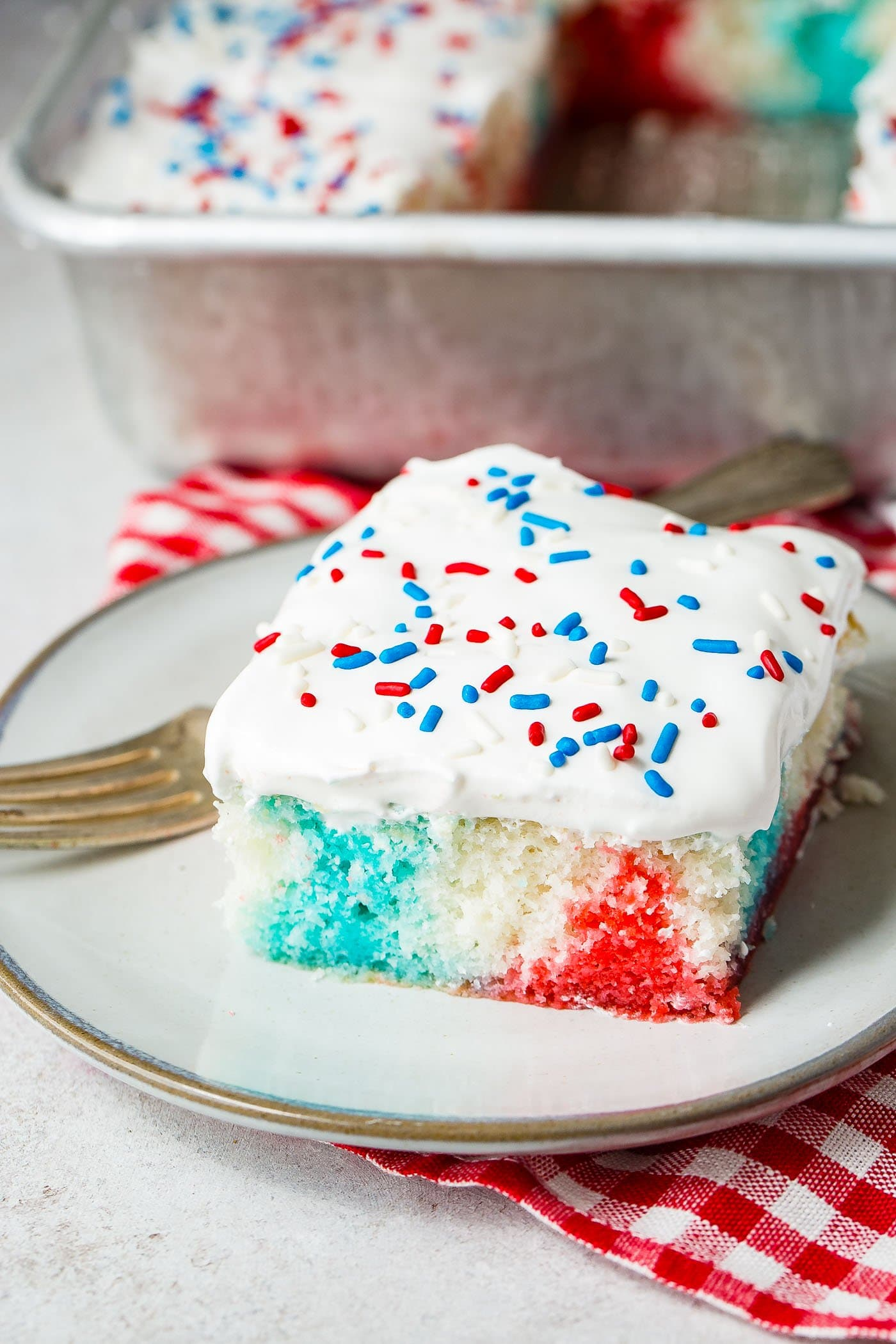 A piece of red, white and blue poke cake on a white dessert plate with a fork resting next to the cake. There is a red and white checkered napkin in the background.