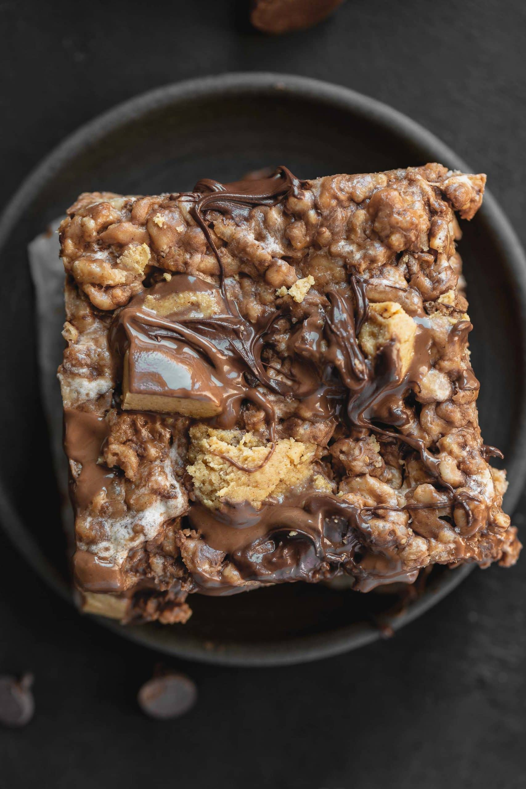 a photo of a single peanut butter rice krispies treat topped with chunks of chopped up reese's peanut butter cups and melted chocolate chips on a dark gray plate
