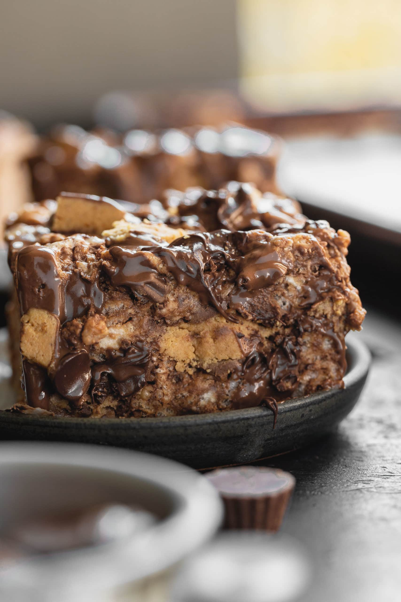 a photo of the cross section of a peanut butter rice krispies treat that is loaded with chunks of reese's peanut butter cups and melty chocolate chips.