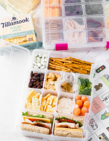 a craft box usually used for beads or other crafts is filled with healthy snacks like nuts, fruits, mini sandwiches, cheese and crackers for a healthy road trip snack box
