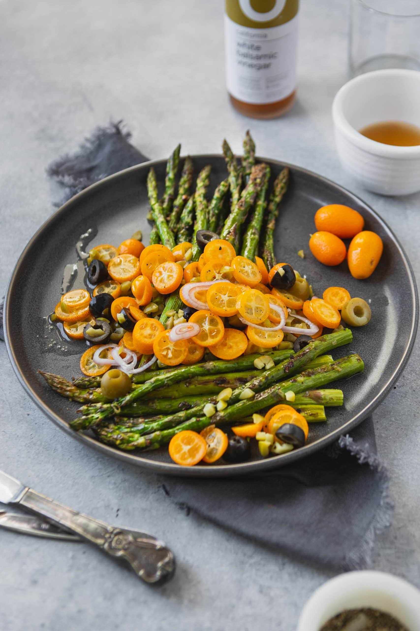 a photo of roast asparagus on a charcoal gray serving dish topped with bright orange sliced kumquats, sliced shallots and sliced black and green olives