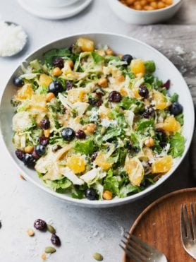 a photo of a large serving bowl full of shredded brussels sprouts salad topped with mandarin oranges, and manchego cheese.