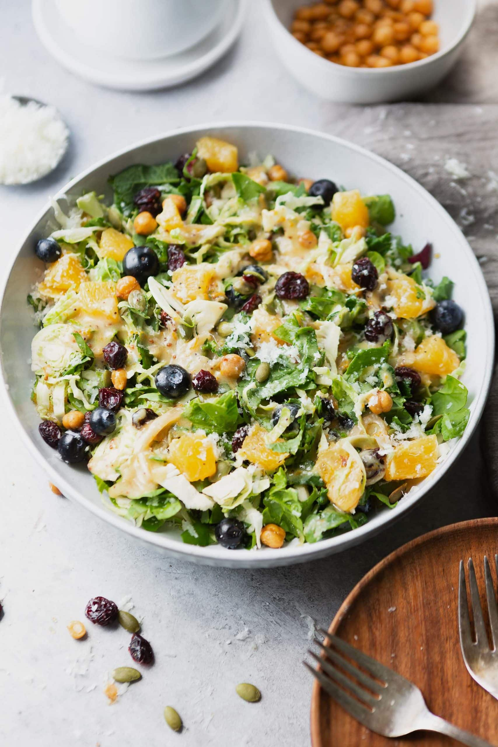 a photo of a large serving bowl full of shredded brussels sprouts salad topped with chunks of oranges, manchego cheese, blueberries, and craisins.