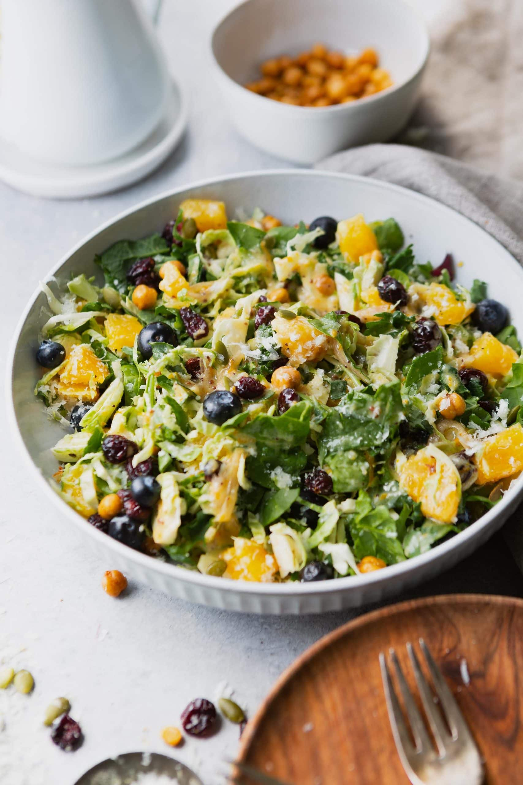 a photo of a large white serving bowl full of mixed greens. the salad has chunks of oranges, blueberries, craisins, roasted chickpeas, and shredded manchego salad in it.