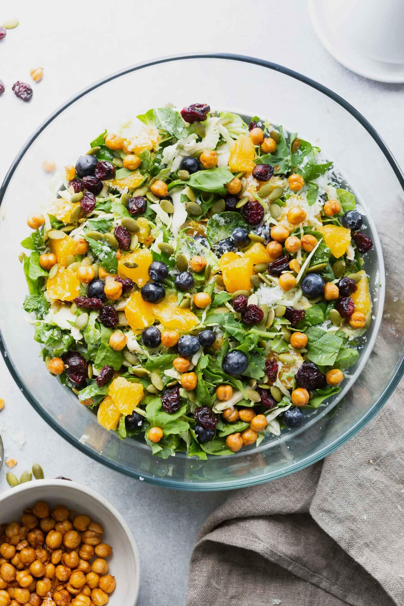 a photo of a large serving bowl full of a salad topped with mandarin oranges, and manchego cheese.
