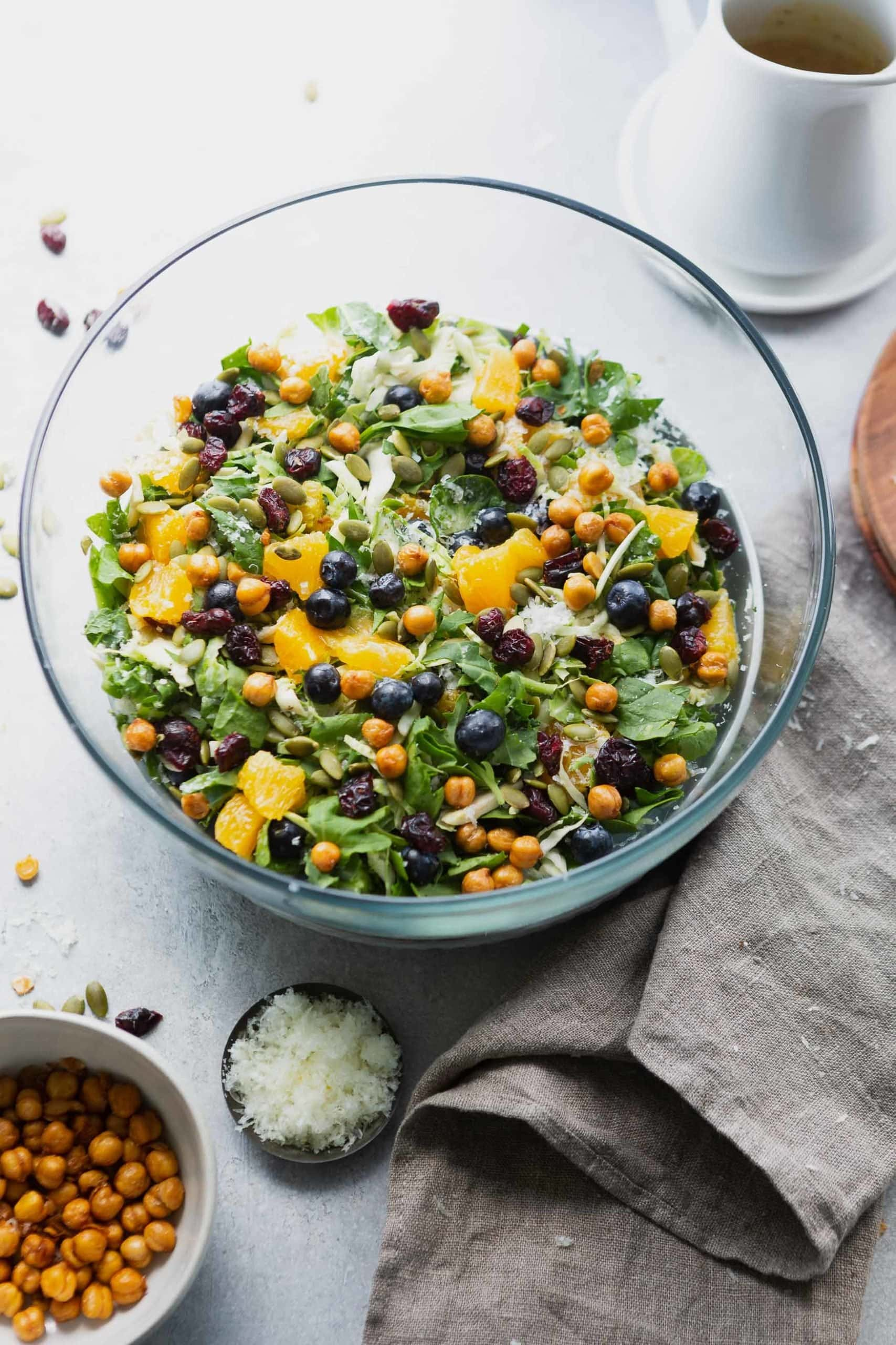 a photo of a large glass bowl full of shredded brussels sprouts salad. you can see whole blueberries, chunks of orange slices, roasted chickpeas, craisins and shredded manchego cheese.