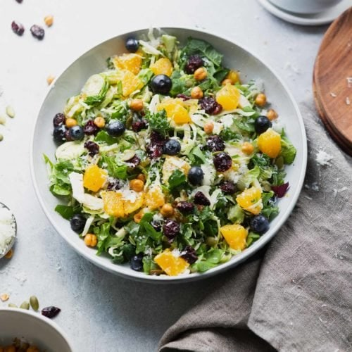 a photo taken above a serving bowl full of shredded brussels sprouts salad topped with chunks of oranges, blueberries, craisins, roasted chickpeas and manchego cheese.