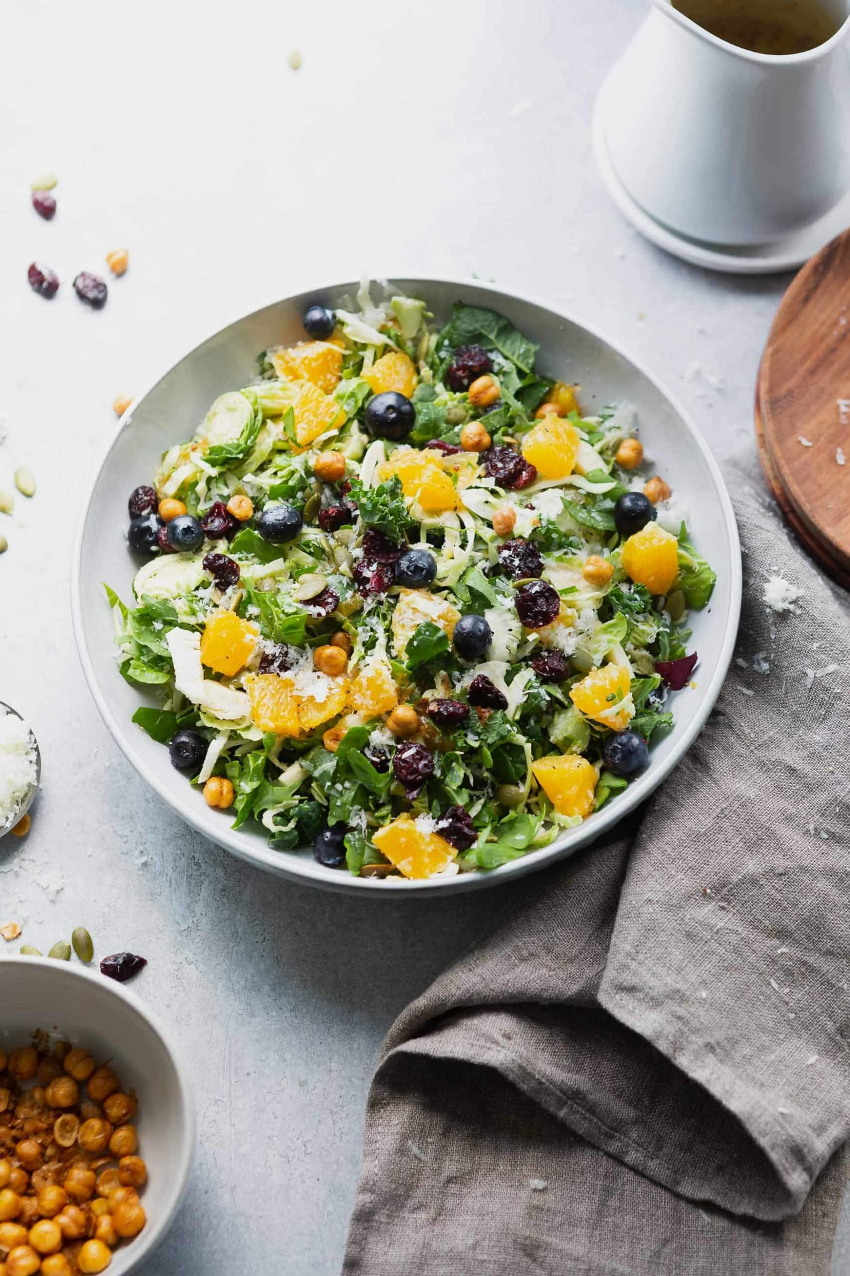 a photo taken above a serving bowl full of mixed greens topped with chunks of oranges, blueberries, craisins, roasted chickpeas and manchego cheese.