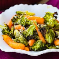 a white bowl with simple roasted garlic veggies including carrots, brussels sprouts and broccoli with a little parmesan cheese