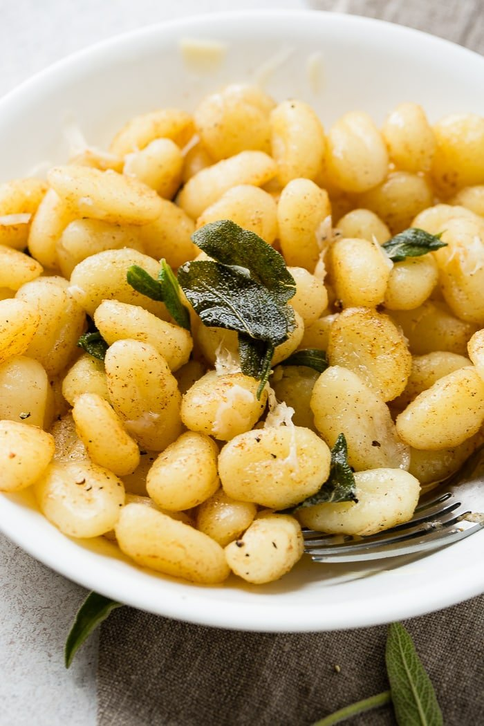 A white bowl with a pile of 10 minute brown butter sage gnocchi on a natural linen naplkin with a fork in the pasta