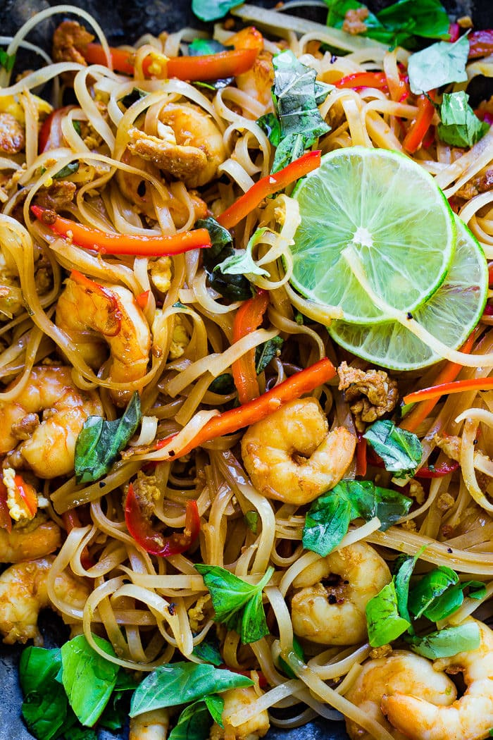 A closeup photo of cooked shrimp, rice noodles, red bell peppers, and fresh basil leaves on a blue plate garnished with slices of lime.