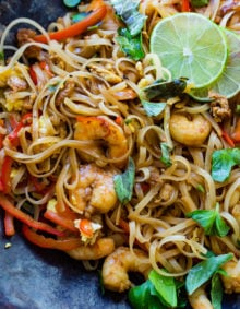 A photo of cooked shrimp, rice noodles, red bell peppers, and fresh basil leaves on a blue plate garnished with slices of lime.