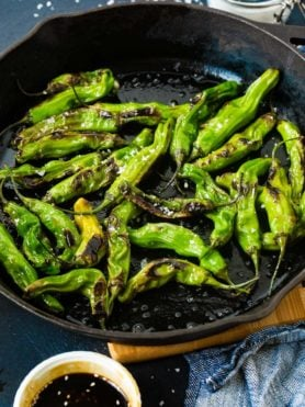 a black cast iron pan with bright green blistered shishito peppers and flaked sea salt