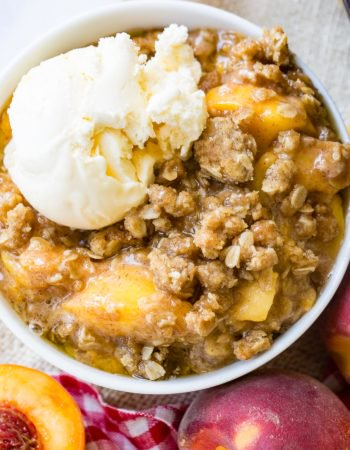 A photo of a bowl of peach crisp with a scoop of vanilla ice cream on top.