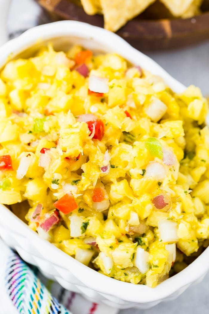 a white pineapple dish with fresh pineapple salsa, peppers and cilantro and red onions