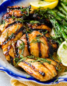 A photo of grilled honey lemon basil chicken thighs with fresh basil chiffonade on top.