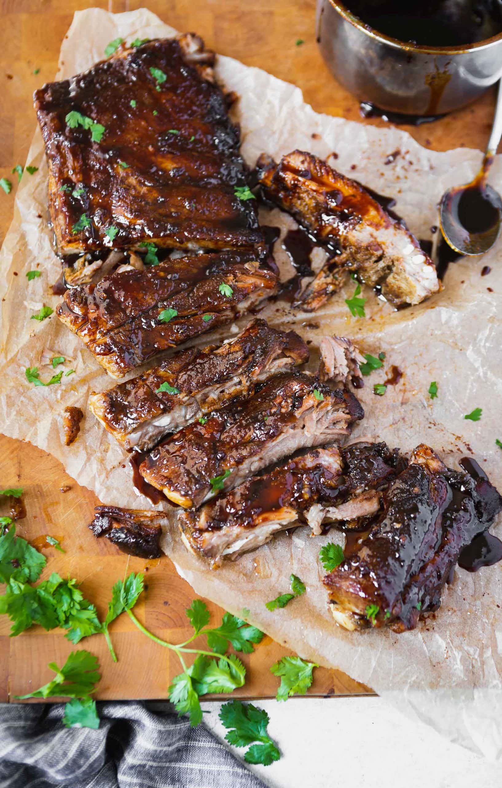 a photo of a rack of asian sticky ribs that have been cut apart into individual ribs all sitting on a piece of parchment paper.