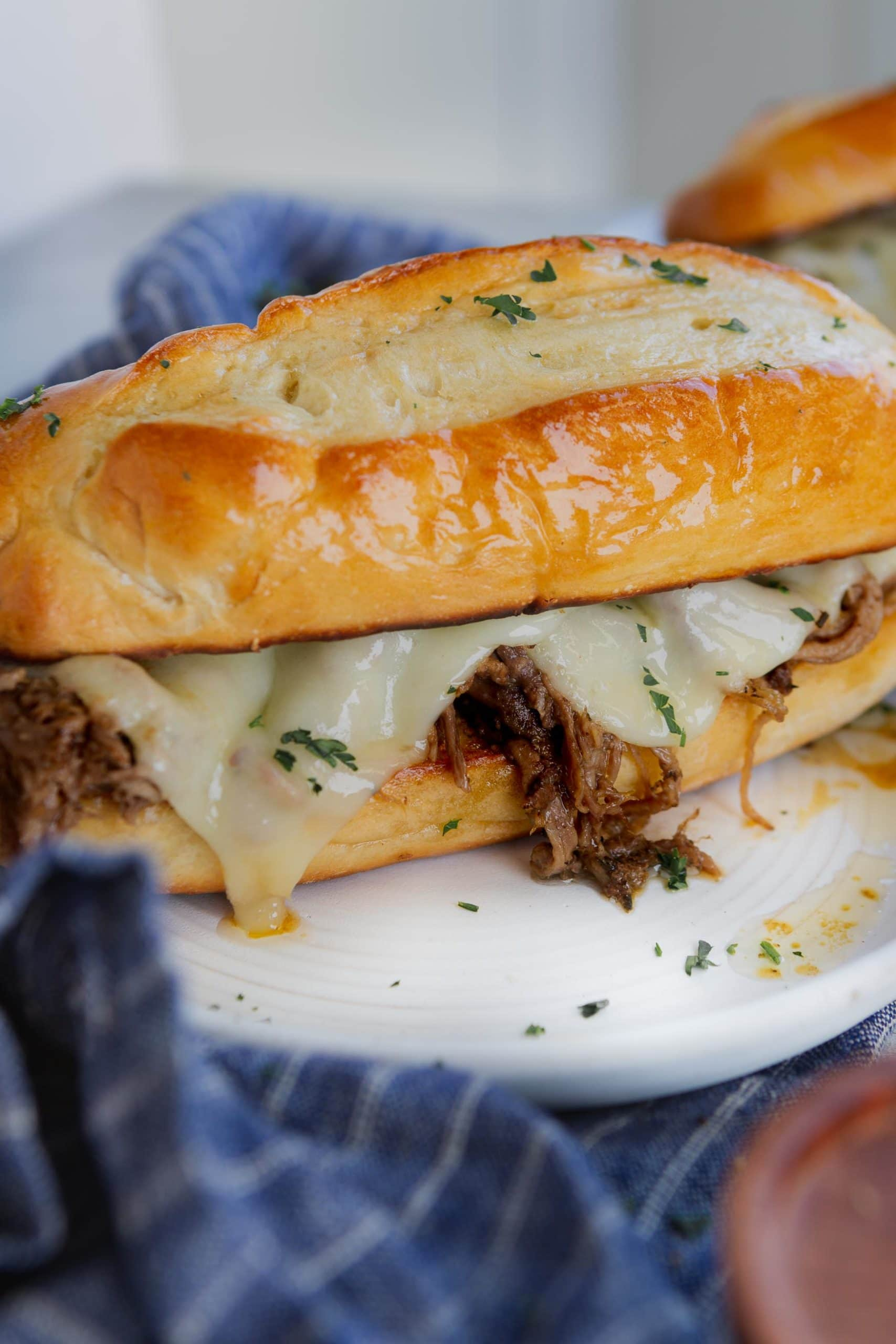 A French dip sandwich. The sandwich is on a hoagie roll and there is beef and melted cheese. The sandwich is on a plate and a blue and white napkin is under the plate.