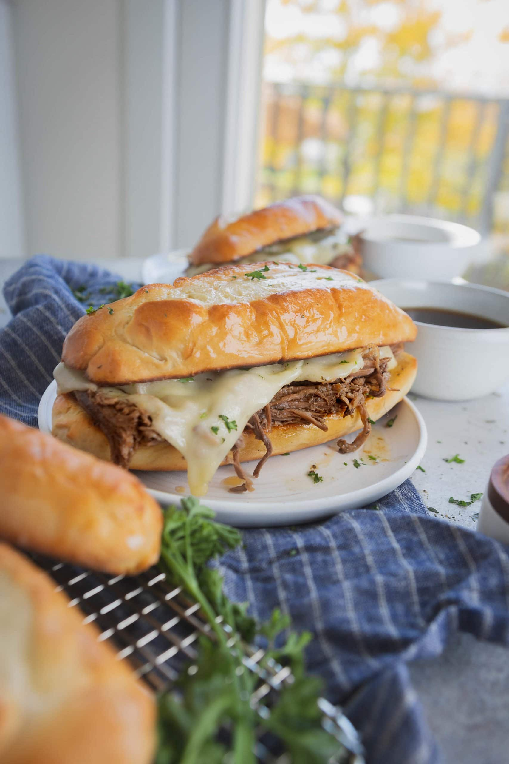 A French dip sandwich on a white plate. The cheese is melted over the beef. Another sandwich is in the background and two hoagie rolls are sitting on the table.
